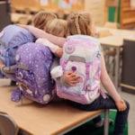 Drei Mädchen in Schule auf Tisch sitzend mit Beckmann Schulranzen Modell 2020 Unicorn von hinten