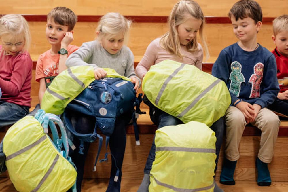 Kinder in Sporthalle stülpen Regenhülle Beckmann Schulranzen Modell 2020 Spaceship