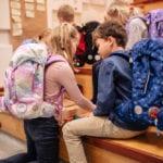 Mädchen und Junge auf Holztreppe besprechen Hausaufgaben mit Beckmann Schulranzen Modell 2020 Unicorn von Seite