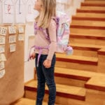 Mädchen auf Holztreppe mit Beckmann Schulranzen Modell 2020 Unicorn von Seite