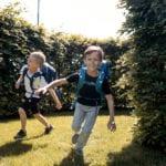 Zwei Jungen rennen im Garten mit Beckmann Schulranzen Modell 2020 Roboman von vorne