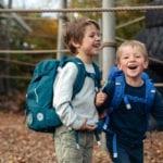 Zwei Jungen haben Spaß auf dem Spielplatz mit Beckmann Schulranzen Modell 2020 Roboman von vorne