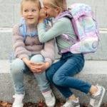 Zwei Mädchen auf Steintreppe flüsternd mit Beckmann Schulranzen Modell 2020 Unicorn von vorne