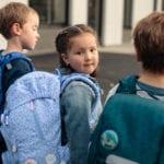 Mädchen mit zwei Jungen auf dem Schulhof mit Beckmann Schulranzen Modell 2020 Ballerina von hinten