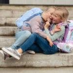 Zwei Mädchen albern auf Steintreppe mit Beckmann Schulranzen Modell 2020 Ballerina