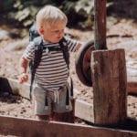 Junge spielt im Sandkasten mit Beckmann Kindergarten Rucksack Modell 2020 fire truck
