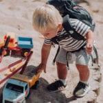 Junge spielt mit LKW im Sandkasten mit Beckmann Kindergarten Rucksack Modell 2020 fire truck