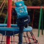 Junge spielt auf Spielplatz am Klettergerüst mit Beckmann Kindergarten Rucksack Modell 2020 Forest