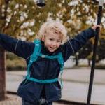 Junge klettert auf Spielplatz auf Seilen mit Beckmann Kindergarten Rucksack Modell 2020 Forest