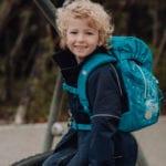 Junge sitzt auf Klettergerüst auf Spielplatz mit Beckmann Kindergarten Rucksack Modell 2020 Forest