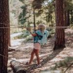 Mädchen klettert im Wald auf Seilen mit Beckmann Kindergarten Rucksack Modell 2020 Unicorn