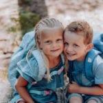 Zwei Kinder sitzen im Wald auf Seilen mit Beckmann Kindergarten Rucksack Modell 2020 Unicorn