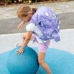 Mädchen steigt auf blaue Kugel und trägt Beckmann classic Dream Seite