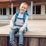 Junge sitz auf Holz Boden und trägt Beckmann classic Galaxy vorne