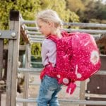 Mädchen hält sich an Stange fest und trägt Beckmann classic Forest Deer red seite