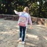 Mädchen balanciert auf stamm und trägt Beckmann Unicorn active air hinten