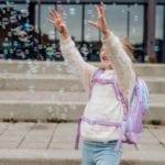 Mädchen fängt Seifen Blasen und trägt Beckmann Unicorn active air schräg vorne