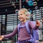 Mädchen bewundert Seifen Blasen und trägt Beckmann Dream active air flx schräg vorne